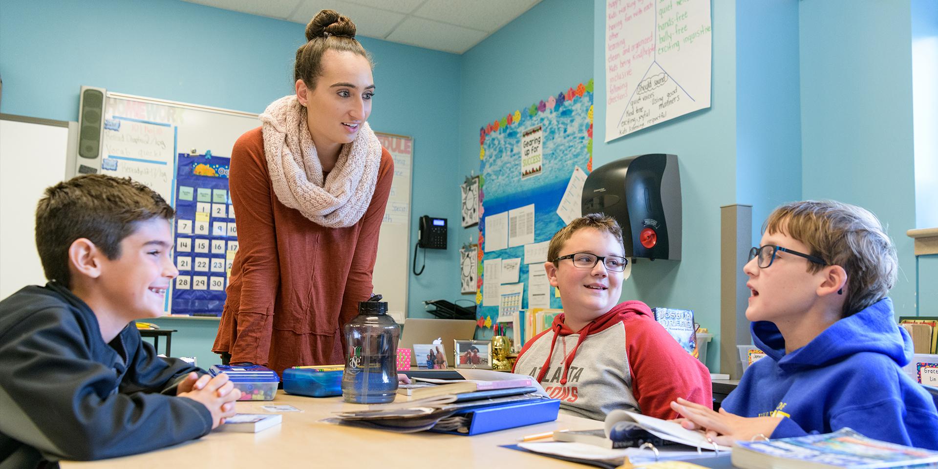 Student teacher talks to three elementary school students