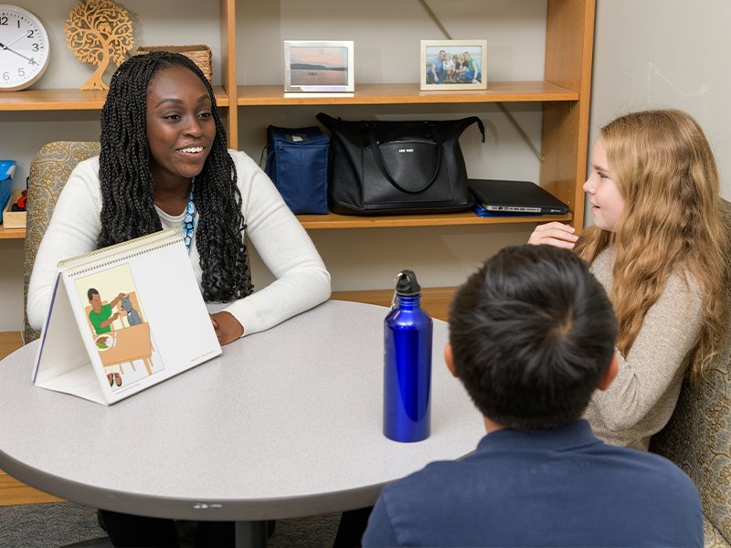 School psychology student speaks with two students at The College School