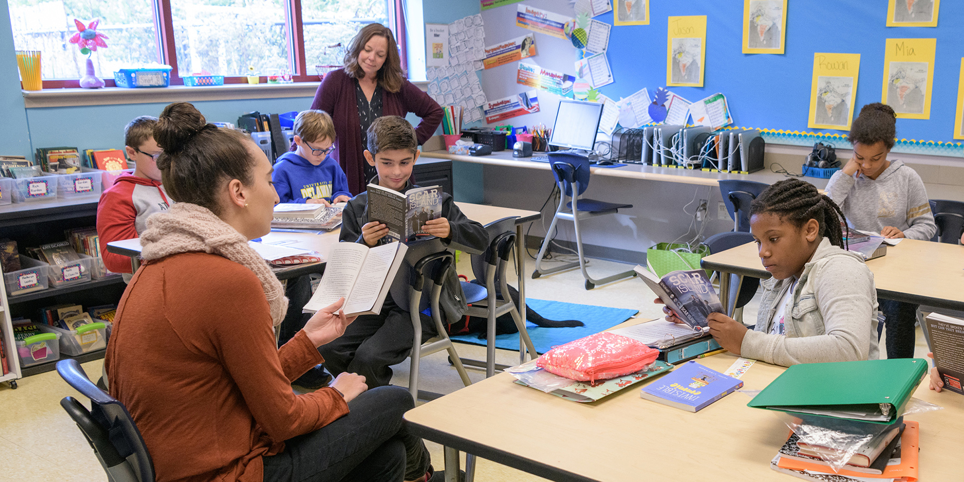Student teacher reading to class as clinical educator observes