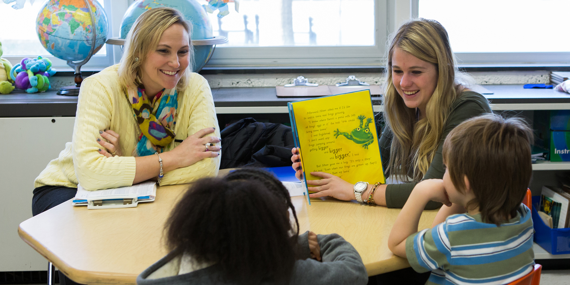 Two student teachers read to children