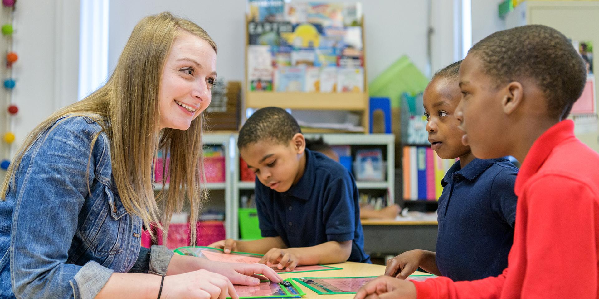 Student teacher speaking to three children